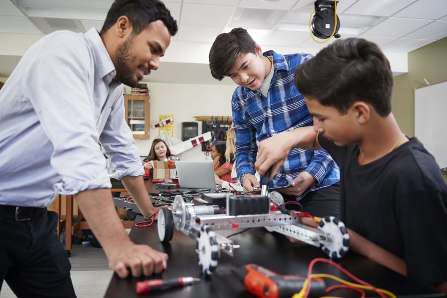 Teacher with students building robots